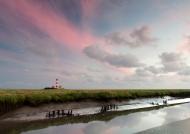 Der Leuchtturm von Westerhever mit einem Priel im Vordergrund kurz nach Sonnenuntergang