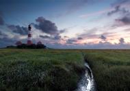 Der Leuchtturm von Westerhever mit bunten Abendhimmel und einem Priel