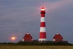 Der Leuchtturm von Westerhever mit aufgehendem Vollmond über dem Horizont