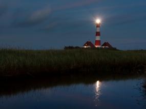 Der Leuchtturm Westerheversand spiegelt sich in einem Priel