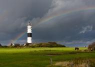 Der Leuchtturm in Kampen auf Sylt mit Regenbogen am Horizont kurz nach einem Gewitterschauer
